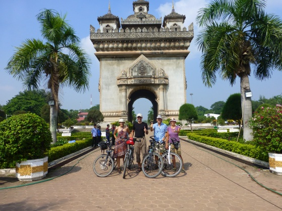 Four cyclists in front of the Patuxai monument
